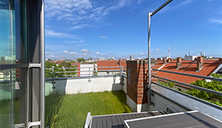 A grassy terrace next to a glass-walled office interior, with a bright blue sky and the Berlin TV tower on the horizon.
