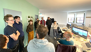 The bitcrowd team standing in a circle discussing, in a large bright office, next to desks with computers and monitors.